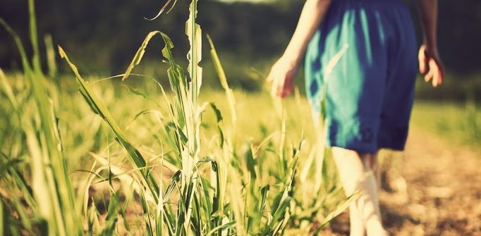 A girl in a blue dress walking in farm